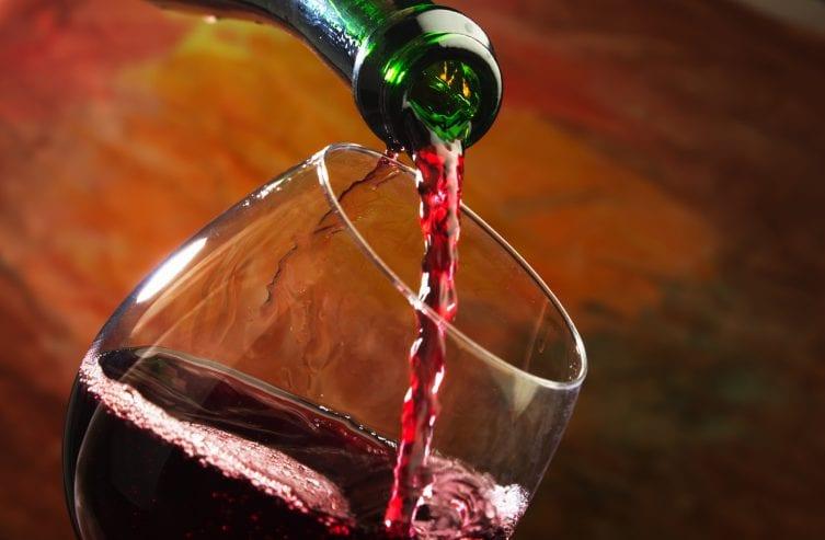 Rotwein wird in Weinglas gegossen
