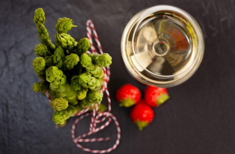 Grüner Spargel mit Weißwein und Erdbeeren auf Schiefer, Topshot.